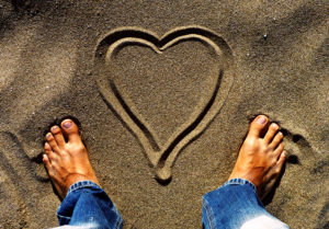 Männerfüße im Sandstrand mit gemaltem Herz: Der neue Mann hat Herz.