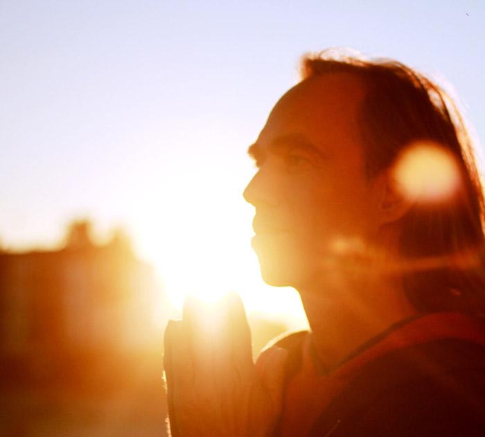 Foto von Soul Guide Michael im Licht eines Sonnenuntergangs, in die Ferne schauend, die Hände wie zum Geben zusammen liegend. Dieser Mann steht klar und fest in der physischen Welt und in der Lichtwelt.
