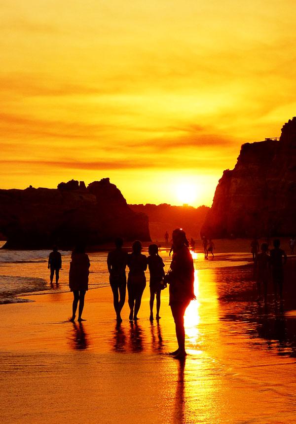 Foto von Menschen am Strand, die alle auf den Sonnenuntergang in der Bildmitte schauen. Der Himmel brennt, der Sand ist nass und spiegelnd. Eine sehr lichtvolle Atmosphäre.  Das Bild steht für die Menschen, die gemeinsam in Richtung des Lichts schauen - die ein gemeinsames Ziel vor Augen haben: den Beginn der Neuen Zeit.