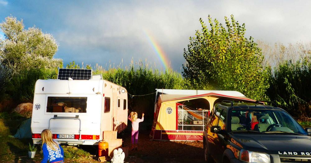 Foto von Wohnwagen, Transporter, Vorzelt, Landrover, spielenden Kindern und einem Regenbogen in freier natur. Der Himel ist teils blau, teils bewölkt. Die Bäume grün und teils blühend. Der Regenbogen ist in der Bildmitte, die Fahrzeuge von der Sonne angestrahlt. Diese Leute leben tatsächlich in und mit der Natur.