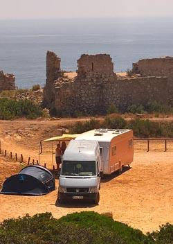 Foto von unserem Transporter und Wohnwagen direkt bei einer historischen Ruine am Rand der Algarve. Geführt vom Flow unserer Seele.